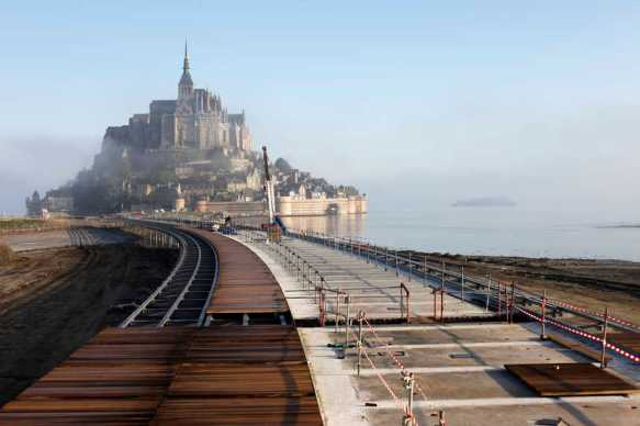 AU PETIT MATIN, VUE DU PONT PASSERELLE DEVANT LE MONT SAINT MICHEL DANS LA BRUME. LE PLATELAGE BOIS EST EN COURS DE POSE. DES OUVRIERS PRƒPARENT LA POSE DU FERAILLAGE ET DES DALLES DE BƒTON PRƒFABRIQUƒES. TRAVAUX RE RƒTABLISSEMENT DU CARACTéRE MARITIME DU MONT SAINT MICHEL. LE MONT SAINT MICHEL, NORMANDIE, FRANCE. AVRIL 2013
